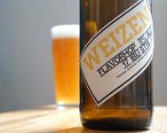 Weizenbier Flasche mit Etikett, im Hintergrund Bierglas